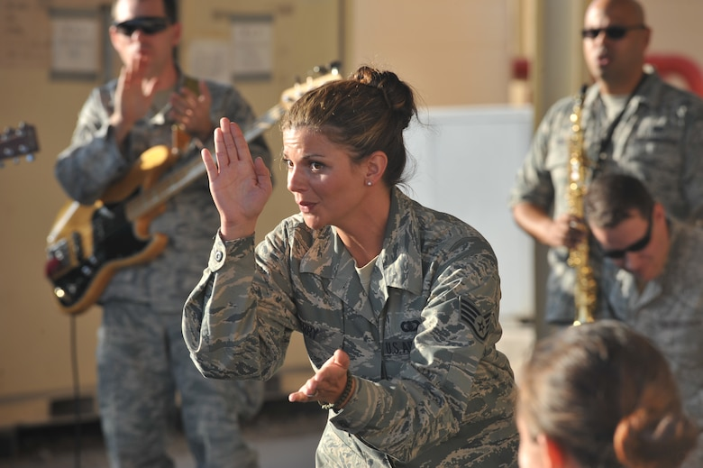 Staff Sgt. Kelly Perry sings to service members at the 8th Expeditionary Air Mobility Squadron passenger terminal, 379th Air Expeditionary Wing, Southwest Asia on Nov. 27, 2013. Systems Go is the newest AFCENT U.S. Air Forces Central Command rock  band and will provide performances to increase troop morale, diplomacy, and outreach to host nations. Perry is a vocalist and is deployed from Wright-Patterson Air Force Base, Ohio, and hails from Louisville, Ky. (U.S. Air Force photo/Master Sgt. David Miller)