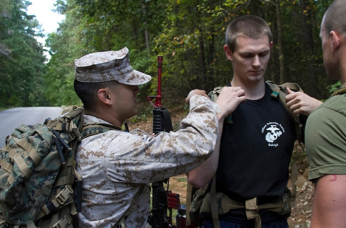 Staff Sgt. Jose Benavidez, an Officer Selection Assistant with Officer Selection Office Raleigh, Marine Corps Recruiting Station Raleigh, helps an officer candidate with his gear during a three-mile hike aboard Umstead Park in Raleigh, N.C., Sept. 28, 2013. The candidates and Marines carried packs with 40 pounds of gear and an M-16 replica rubber rifle to get a feel for hiking while carrying weight.  (U.S. Marine Corps photo by Sgt. Dwight A. Henderson/Released)