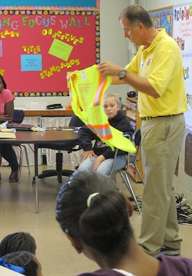Pat Haas, Huntsville Center engineer and Director of Chemical Demilitarization Directorate, shows students how engineers use safety equipment in a field environment during Career Day Sept. 27.