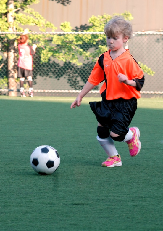 Kaylee Turner, daughter of Master Sgt. John Turner Jr., dribbles the ball during her team's first youth soccer game at Osan Air Base, Republic of Korea, Sept. 25, 2013. As a member of the Dragons, age 5-6 division, Turner learns basic fundamental skills and rules of soccer during the season. Youth sports are made possible by dedicated volunteer coaches from the base community. If interested in volunteering for seasonal youth sports, contact the director of youth sports by emailing matthew.sharman@us.af.mil. (U.S. Air Force photo/1st Lt. Kay M. Nissen)