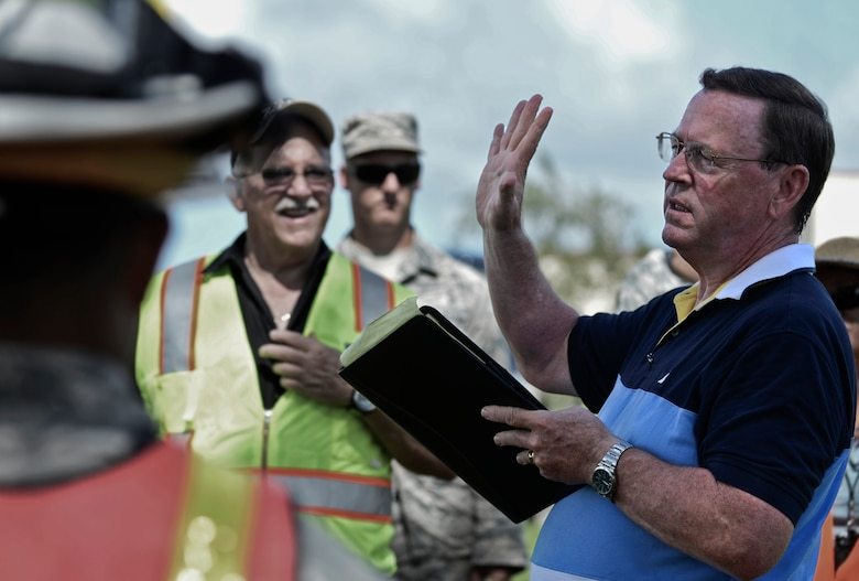 Michael Donohoe, ¬¬ Defense Logistics Agency preparedness and planning head contractor, discuss Team Andersen's performance during the annual multi-agency fuel spill response training event Sept. 26, 2013, at the 36th Logistics Squadron Fuels Management Flight compound on Andersen Air Force Base, Guam. The training was conducted to comply with the provisions of the Oil Pollution Act of 1990, which states parties responsible for a vessel or facility from which oil or fuel is discharged and poses a substantial threat of a spill must have a plan to prevent spills that may occur and a detailed containment and cleanup plan. (U.S. Air Force photo by Senior Airman Marianique Santos/Released)