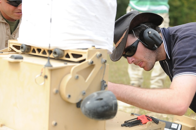 Matt Cork, 24, field technician, Marathon Targets, Sydney, Australia,  repairs a T-40 robot that broke down during a live-fire exercise at Range 12 aboard Marine Corps Base Quantico on Sept. 20, 2013.  The robots have three modes operators can choose from when firing.