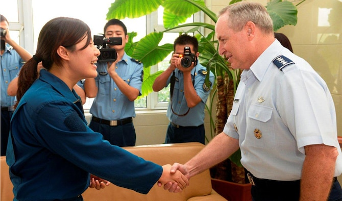 "Air Force Chief of Staff Gen. Mark A. Welsh III greets a pilot from the People's Liberation Army Air Force Sept. 27, 2013, at Nanyuan Air Base, China. Welsh, along with Gen. ""Hawk"" Carlisle and Chief Master Sgt. of the Air Force James A. Cody, visited with various military leaders as part of a weeklong visit to China."