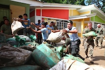 Filipino police officers, community members and soldiers as well as U.S. Marines toss potato sacks filled with mud as part of a community relations event Sept. 29 at Olongapo City, Zambales, Republic of the Philippines during the Amphibious Landing Exercise 2014. The team helped clean three flood-affected schools. Bilateral Philippine-U.S. Marine Corps training during PHIBLEX sustains and reinforces the foundation and framework for a bilateral force to respond rapidly and effectively to regional humanitarian crises. The Filipino soldiers are with the Army Reserve Command. The Marines are with 3d Marine Expeditionary Brigade, III Marine Expeditionary Force. (U.S. Marine Corps photo by Lance Cpl. Jose D. Lujano/ Released)