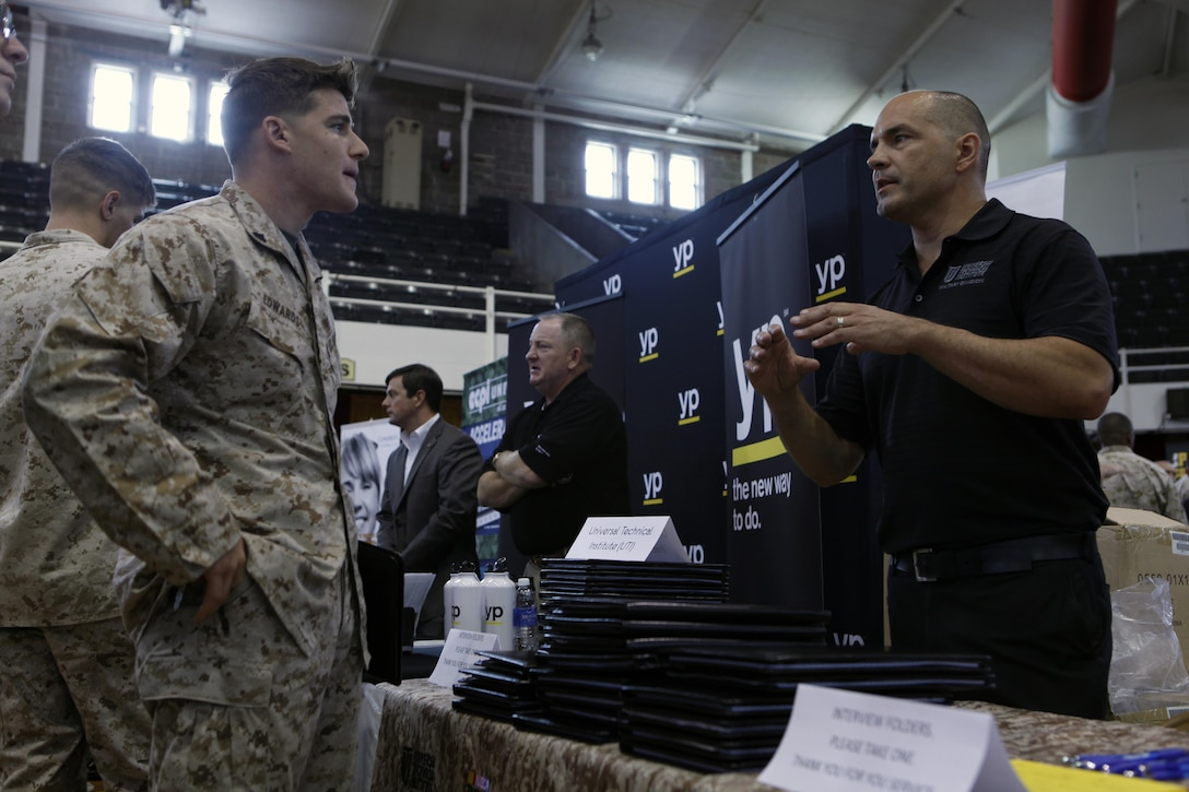 Cpl. Zachary D. Edwards, an infantrymen with 3rd Battalion, 6th Marine Regiment, talks with Jason Hejlik, a military adviser representative with Motorcycle and Marine Institute, about possible employment and education opportunities during the National Job Fair and Education Expo at the Goettge Memorial Field House aboard Marine Corps Base Camp Lejeune, Sept. 25.