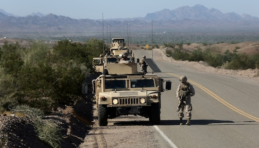 Marines with Baker Company, 1st Battalion, 7th Marine Regiment, patrol around their vehicles during a training convoy here, Sept. 24, 2013. The Baker Co. Marines drove two Mine Resistant, Ambush Protected All Terrain Vehicles and two armored Humvees to a turnaround point nearly an hour away and then returned to their starting point. The training was designed to be a basic introduction for patrolling with vehicles.
