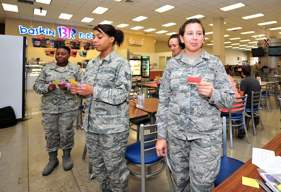 Airmen stand in silence while holding cards showing statistics about breast cancer and domestic violence during a Breast Cancer and Domestic Violence Awareness Month flash mob at Osan Air Base, Republic of Korea, Oct. 1, 2013. Approximately 25 people took a stand in the base Exchange food court to show their support for finding a cure for breast cancer and to encourage sufferers of domestic violence to speak out. (U.S. Air Force photo/Airman 1st Class Ashley J. Thum)