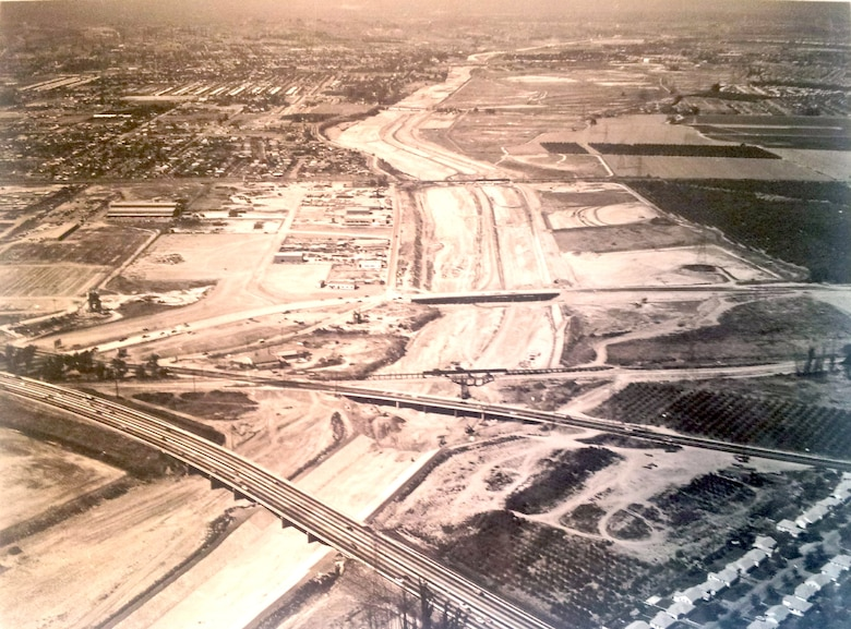 View looking upstream from the lower limits of the channel showing partially excavated and graded channel.  Santa Ana Freeway is in the foreground.