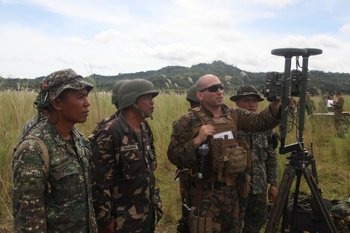 U.S. Marine Sgt. Reid L. Griffin discusses the purpose of establishing a proper orientation for directing a M101 105-mm Towed Howitzer with Philippine Marine and Army personnel during Amphibious Landing Exercise (PHIBLEX) 2014 at the Crow Valley Range Complex in Tarlac province, Republic of the Philippines. Bilateral Philippine-U.S. Marine Corps training sustains and reinforces the foundation and framework for a bilateral force to respond rapidly and effectively to regional humanitarian crises. Griffin is an artillery meteorological man with Battalion Landing Team 1st Battalion, 4th Marine Regiment, 13th Marine Expeditionary Unit. (Photo by Lance Cpl. David Hersey)