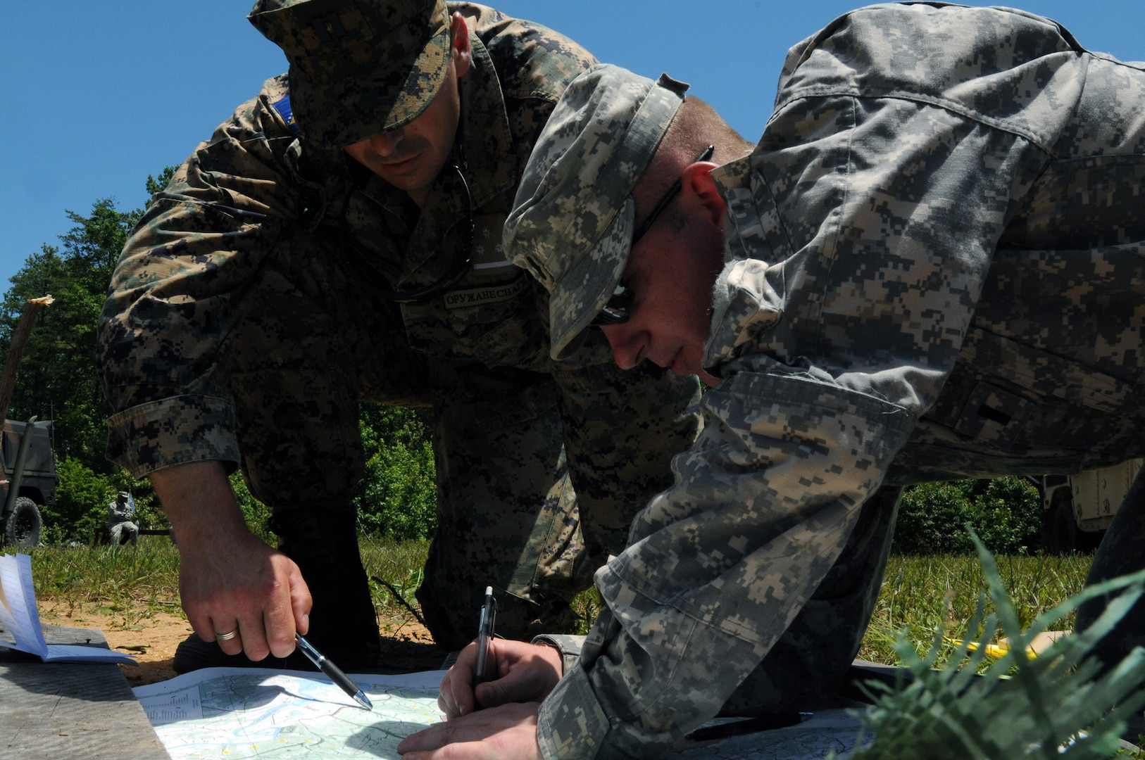 Armed Forces of Bosnia-Herzegovina Capt. Drgan Malic, left, company commander, and Army 1st Lt. Jeff Hartline, of Company C, 1st Battalion, 175th Infantry Regiment, plot out features on a map in order to complete a sand table for a combat lane exercise during training at Fort A.P. Hill, Va., June 15, 2012. AFBiH soldiers were embedded with Maryland Army National Guard units throughout the duration of training here and at Camp Dawson, W.V. Bosnia-Herzegovina and the Maryland National Guard are partnered through the National Guard Bureau's State Partnership Program.