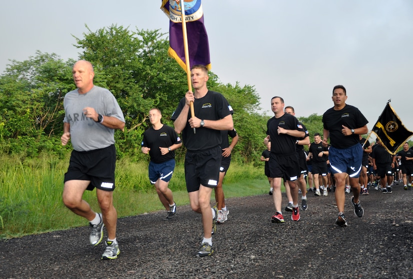 """U.S. Army Col. Thomas Boccardi, Joint Task Force-Bravo commander, leads the way during an """"Esprit de Corps"""" run at Soto Cano Air Base, Honduras, Oct. 4, 2013.  The formation run was conducted for servicemembers to exhibit pride and esprit de corps within the organization while improving physical fitness.  Boccardi addressed the servicemembers prior to the run and thanked them for their outstanding work and commitment to the mission of JTF-Bravo.  (U.S. Air Force photo by Capt. Zach Anderson)"""