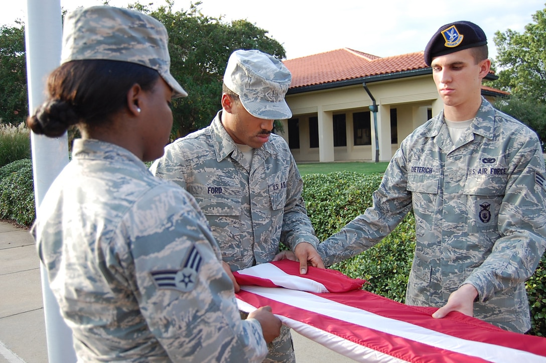 Maxwell Air Force Base Airman Leadership School class 13-7 folds the flag while conducting retreat, Oct. 3. Despite budgetary constraints, ALS is continuing here throughout the government shutdown. (Courtesy photo)