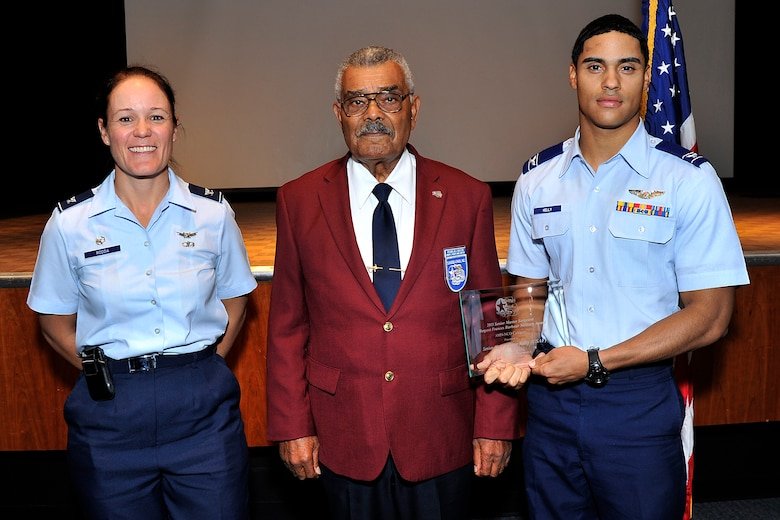Cadet Candidate Ryan Kelly (right) receives the Senior Master Sgt. Margaret Barbour Frances Award from Tuskegee Airman Franklin J. Macon (middle) and Col. Kabrena Rodda at the Community Center Theater Sept. 26. The award is presented to a noncommissioned officer who has exhibited outstanding performance in both professional and community service. (U.S. Air Force Photo/Sam Lee)