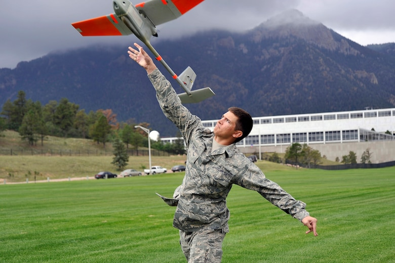 Cadet 2nd Class Jeremy Snell launches the RQ-11 Raven, a small hand-launched remote-controlled unmanned aerial system, at the Stillman Parade Field. Cadets will soon become evaluators in the Academy's unmanned aerial system program. (U.S. Air Force Photo/Liz Copan)