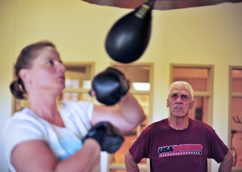 Danny Graves watches on as Jessica Toreno practices her boxing technique on the speed bag at the base gym at Fairchild Air Force Base, Wash., Sept. 19, 2013. Graves runs the boxing clinic for amateur boxers and beginners at the fitness center on base. (U.S. Air Force photo by Senior Airman Taylor Curry/Released)