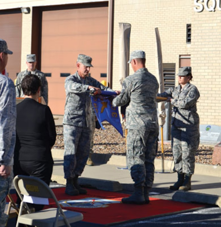 During a flag furling ceremony Sept. 30, Col. Matthew Harris, 3rd Combat Communications Group commander, left, and Chief Master Sgt. Brian Dickirson, group superintendent, right, officially inactivate the 3rd Herd. Assisting is Master Sgt. Megan Giacchetta. (Air Force photo by April McDonald)