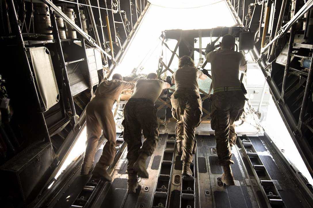 Senior Airman Zac Sidders, 774th Expeditionary Airlift Squadron loadmaster, assists aerial porters from the 455th Expeditionary Aerial Port Squadron pushing cargo off a C-130 Hercules at Bagram Air Field, Afghanistan, Sept. 28, 2013. This mission marked a retrograde milestone as the 774th EAS transported the last cargo from Forward Operating Base Sharana, Paktika province, Afghanistan, before the base is transferred to the Afghan Ministry of Defense. Sidders, a Peoria, Ill., native, is deployed from the Wyoming Air National Guard.