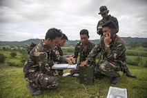 "Members of the Philippine Air Force call in a ""show of force"" mission for two F/A-18C Hornets during close air support training Sept. 29 at Crow Valley, Republic of the Philippines, part of Amphibious Landing Exercise (PHIBLEX) 2014. The day of training qualified the participating PAF members as forward air controllers. PHIBLEX 14 is focused on interoperability between both nations and also improves security and stability within the region. The airmen are with 710 Special Operations Wing. U.S. Marines and sailors from the 13th Marine Expeditionary Unit, 3d Marine Expeditionary Brigade and III Marine Expeditionary Force trained with their Philippine counterparts during the exercise. (Marine Corps photo by Lance Cpl. Anne K. Henry)"