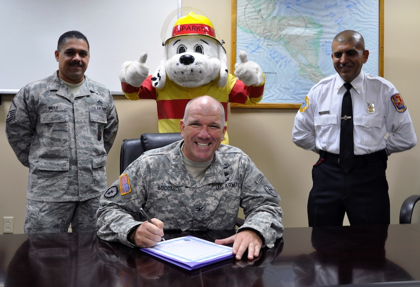 Col. Thomas Boccardi, Joint Task Force-Bravo commander, signs a proclamation declaring Fire Prevention Week at Joint Task Force-Bravo as U.S. Air Force Master Sgt. Juan Valle, Sparky the Fire Dog, and JTF-Bravo fire inspector Herberth Gaekel look on, Oct. 7, 2013. Fire Prevention Week was established to commemorate the Great Chicago Fire of 1871, and now serves as a way to keep the public informed about the importance of fire prevention. (U.S. Air Force photo by Capt. Zach Anderson)