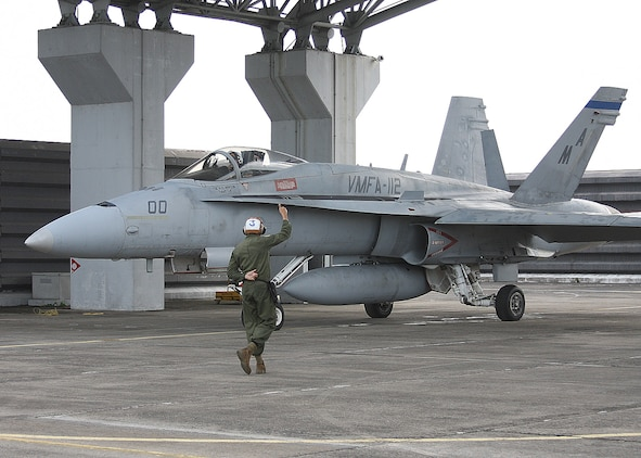 A Marine with Marine Fighter Attack Squadron 112 guides an aircraft along the flightline, Royal Malaysian Air Force Base Butterworth, Malaysia. The Cowboys returned to Iwakuni and are prepareing for their next deployment.