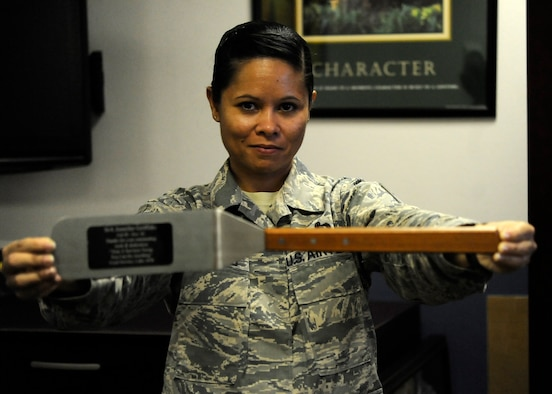 Master Sgt. Jennifer Griffiths, Hurlburt Field Airman Leadership School commandant, holds a spatula in her office at Hurlburt Field, Fla., Oct. 8, 2013. It was given to her as a going away gift when she was a senior airman in services. (U.S. Air Force photo/Staff Sgt. Jeff Andrejcik)