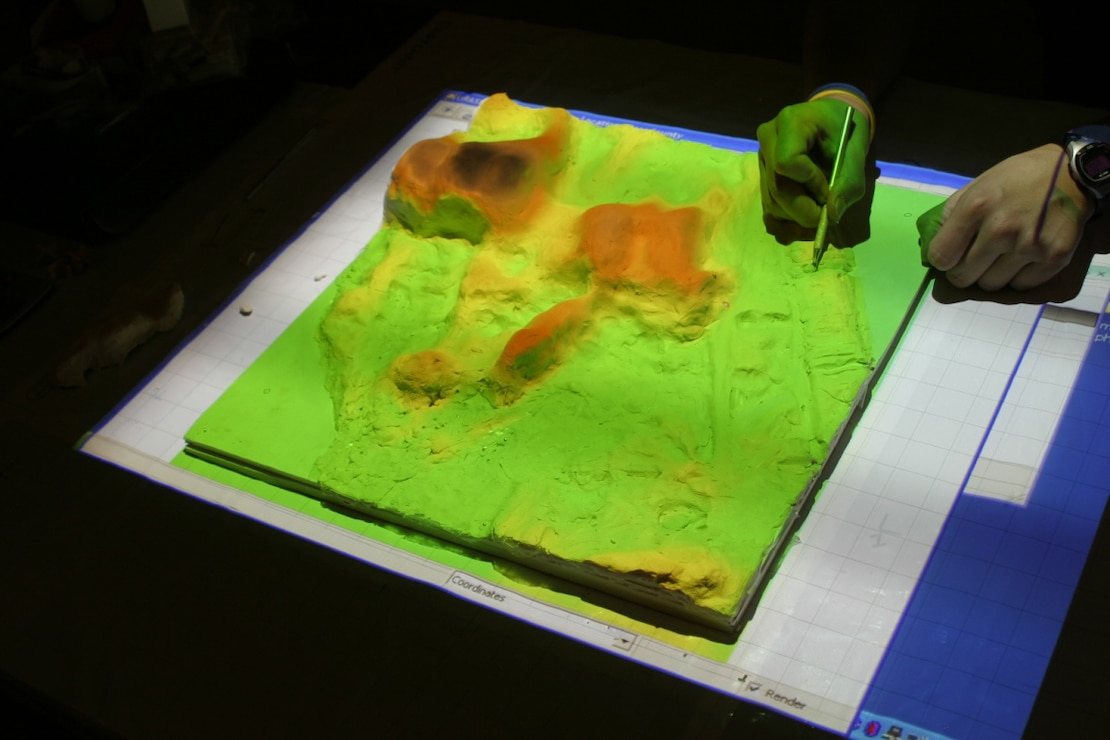 This image shows the Tangible Geospatial Modeling System (TanGeoMS) at North Carolina State University used for analyzing relationships between the morphology of elevation surfaces and dynamic landscape processes.  A flexible physical model can be modified by hand and scanned to create digital representations of altered landscapes within a geographic information system.