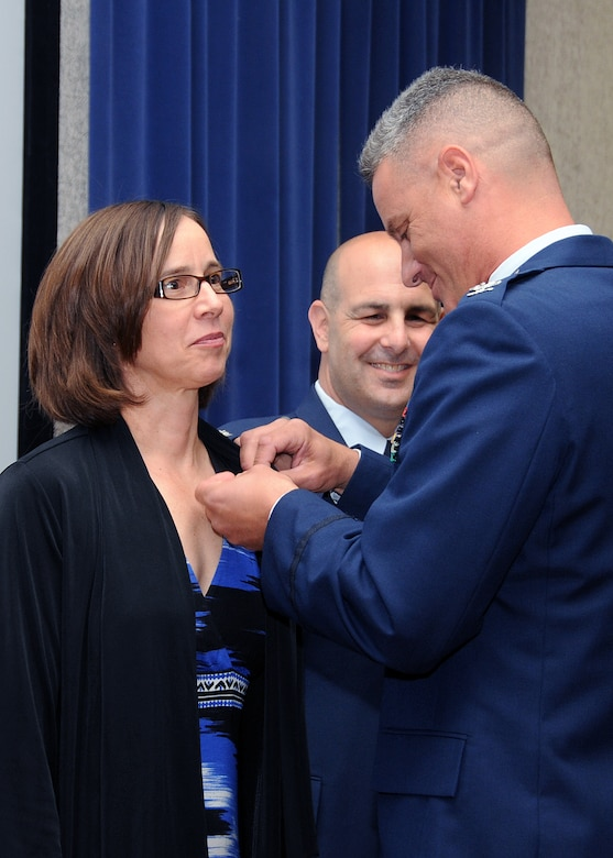 Mrs. Carol Hamel, wife of Colonel Anthony Hamel, Commander, 143d Mission Support Group, is pinned to Brigadier General in the Unorganized Rhode Island Militia following Col Hamel's promotion to Colonel. This is a long standing tradition done to remind Col Hamel of his position in the home. National Guard photo by Master Sgt Janeen Miller