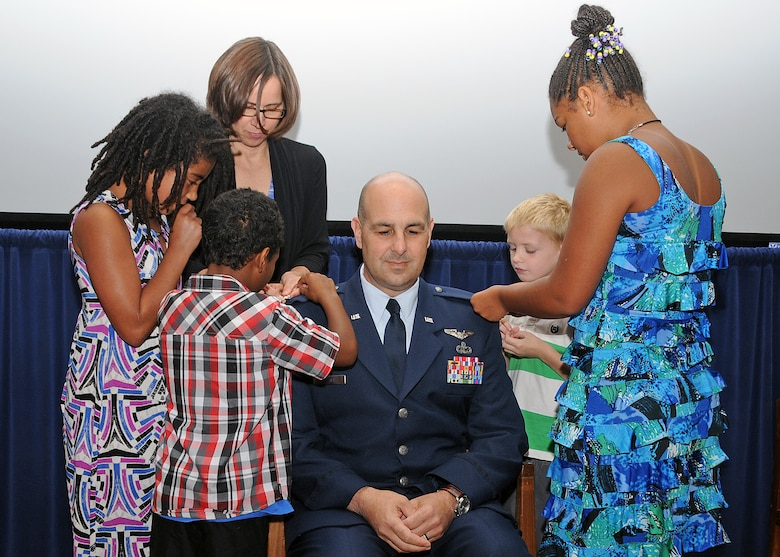 Colonel Anthony Hamel is pinned by his wife Carol and his children Sophia, Grace, Antonio and Andrew. National Guard photo by Master Sgt Janeen Miller