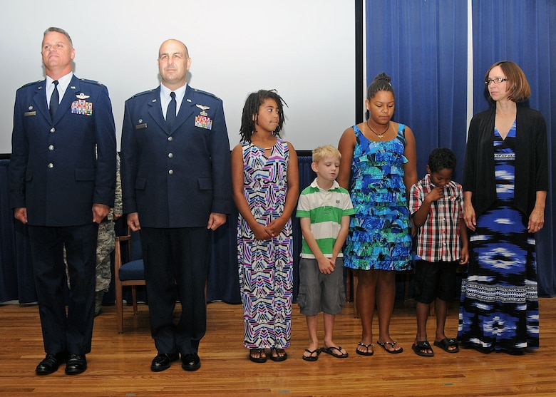 Colonel Arthur Floru, Commander, 143d Airlift Wing, Lieutenant Colonel Anthony Hamel, Commander, 143d Mission Support Group, and LtCol Hamel's family stand for the reading of the promotion order to promote LtCol Hamel to Colonel. National Guard photo by Master Sgt Janeen Miller