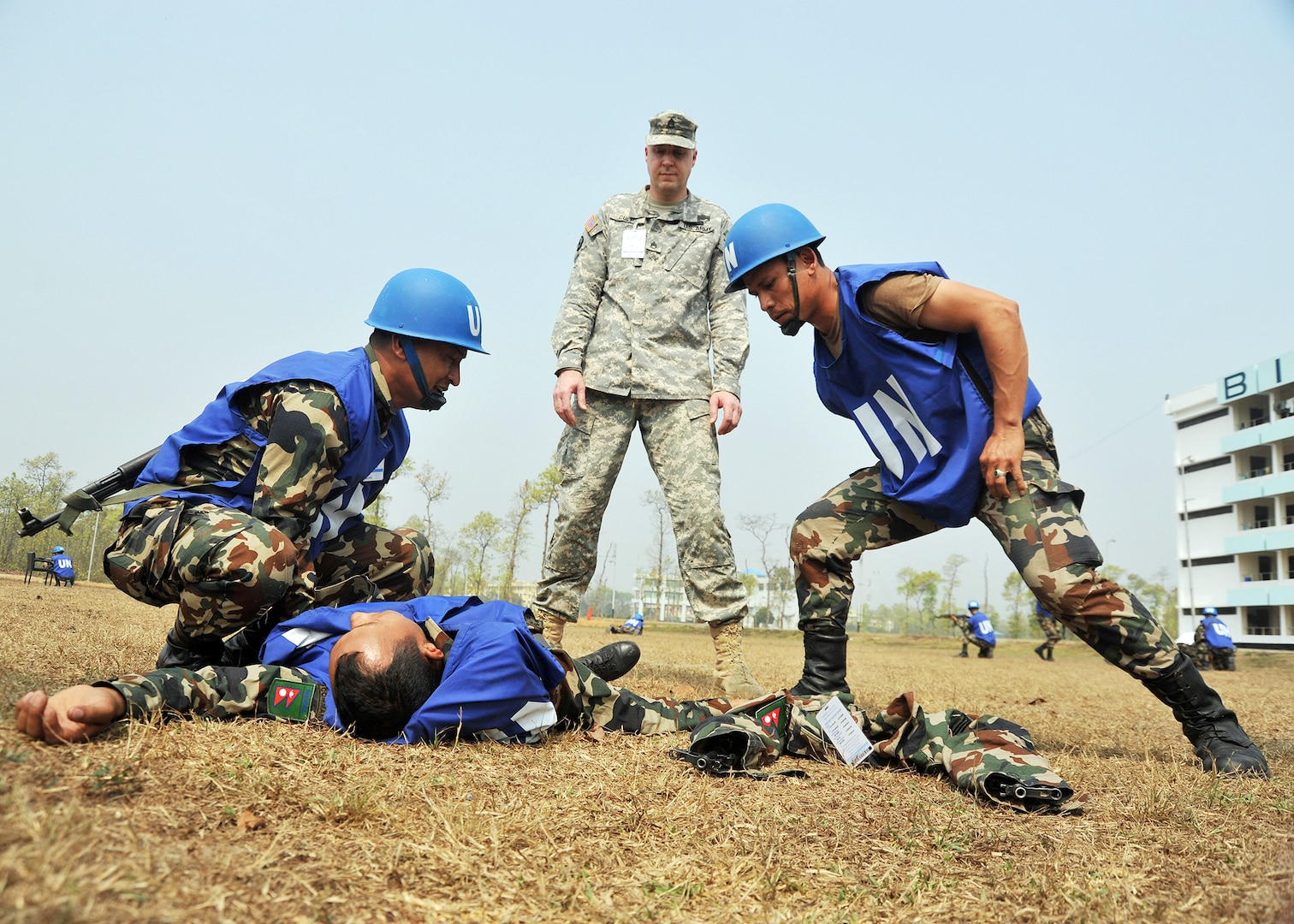 Oregon Army National Guard Staff Sgt. Darrin Culp, of the 249th Regiment Training Institute in Monmouth, Ore., oversees two Nepalese soldiers as they tend to their role-playing comrade during a medical emergency scenario on the first day of Exercise Shanti Doot 3, in Bangladesh March 9. Culp and his fellow Soldiers were invited to participate as a battlefield lifesaving technique instructors through the State Partnership Program between Oregon and Bangladesh. Exercise Shanti Doot 3 is a Bangladesh armed forces-hosted and U.S. Pacific Command Global Peace Operations Initiative supported joint multi-national exercise designed to give operations, logistics, planning and tactical peace-keeping training to members of 13 different countries in preparation for United Nations Peace-keeping Operations.