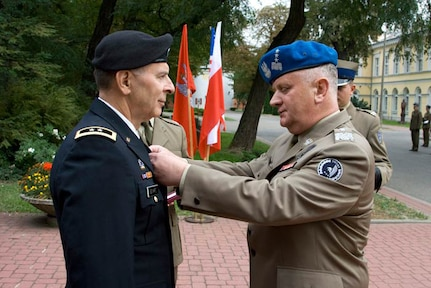 Army Maj. Gen. William Enyart, the adjutant general of the Illinois National Guard, receives the Polish Army Medal from Polish Land Forces Commander Lieutenant General Zbigniew Glowienka on Sept. 23. 2011. The Illinois National Guard and Poland have been partners through the National Guard State Partnership Program since 1993.