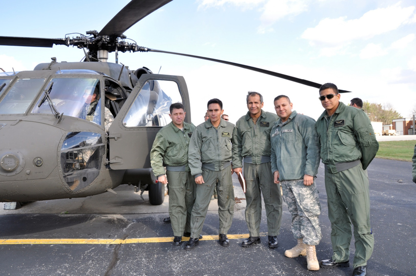The member of the Kentucky Army National Guard 63rd Theater Aviation Brigade stands with the members of the Ecuadorian Army Air Group during their visit at Boone National Guard Center in Frankfort, Ky., Nov. 17, 2011. The Kentucky National Guard hosted a team of aviators and maintainers from the Republic of Ecuador Army Air Group as part of the National Guard State Partnership Program.