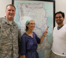 (From left) Lt. Col. John Van Steenburgh, Office of Security Cooperation Chief for Ghana, Togo and Benin; Linda Smittle, Peace Corps Ghana volunteer and Marcelo Maier, U.S. Army Corps of Engineers Europe District special projects engineer pause to point out the location of the Nkwanta Nutritional Rehabilitation Center project on a map of Ghana during a meeting at the embassy in Accra.
