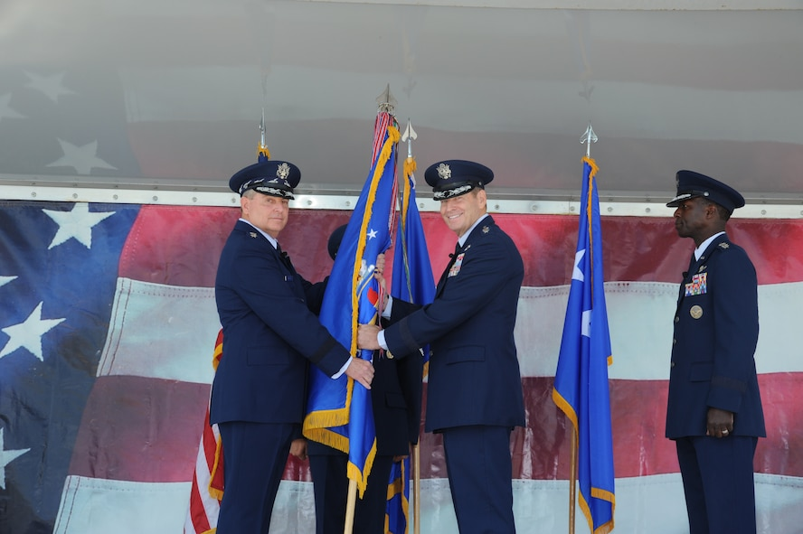 JOINT BASE SAN ANTONIO-RANDOLPH, Texas -- Air Force Chief of Staff Gen. Mark A. Welsh III (left) gives the Air Education and Training Command flag Gen. Robin Rand, officially making him the new AETC commander here Oct. 10. (U.S. Air Force photo by Rich McFadden)