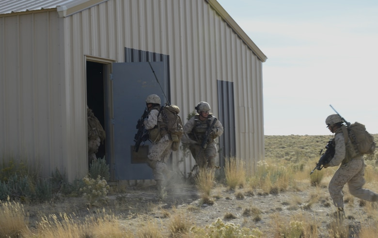 U.S. Marines from the 1st Air Naval Gunfire Liaison Company clear a building during Mountain Roundup 2013 Urban Operations training Oct 8, 2013, at the Juniper Butte range. The 1st ANGLICO team members also called in close air support during the exercise to re-qualify JTACs and to maintain proficiency in their ability to provide CAS, while training with another major coalition partner nation – Germany. (U.S. Air Force photo by Senior Airman Benjamin Sutton/RELEASED)