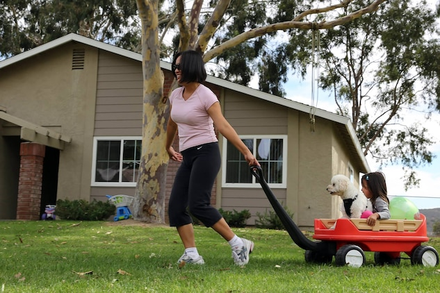 Ayako Hansen plays with her daughter, Lia, and their dog, Shi-sa, in O'Neill Heights Housing where their family were finally able to return after being evacuated, Oct. 5, for a fire that reached 2,500 acres. Lia is 2 years old.