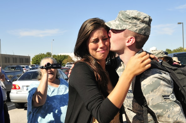 """Airman 1st Class Clint Grunalt, who performs hydraulic maintenance on the E-3 """"Sentry"""" Airborne Warning and Control System aircraft for the 552nd Aircraft Maintenance Squadron, kisses his wife, Sarah, soon after returning to Tinker Air Force Base Wednesday from a six-month deployment to Southwest Asia with about 135 other fellow Airmen, primarily from the 963rd Airborne Air Control Squadron. Also attending the homecoming were Airman Grunalt's parents, John and Dawn Grunalt, and his sister, Ashlynn, who drove all the way from Sterling Heights, Mich., to welcome home their son and brother. Airman Grunalt's grandmother, Mary Jo, made the trip from Amarillo, Texas, as well. Also on hand were a host of Airman Grunalt's in-laws from Warr Acres, as well as several friends. (Air Force photo by Darren Heusel)"""