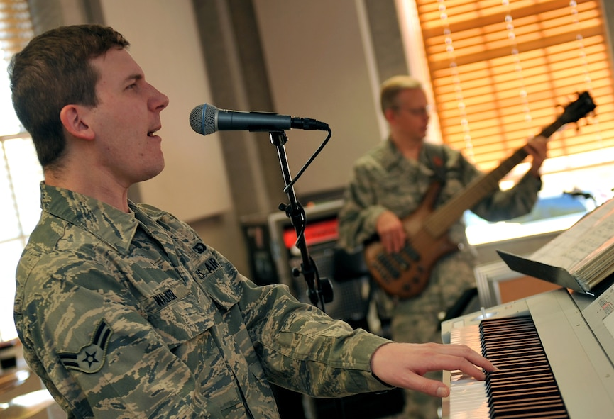 U.S. Air Force Airman 1st Class Adam Walker, a keyboardist for the Heartland of America Band, sings backing vocals during a rehearsal Oct. 10, on Offutt Air Force Base, Neb. The HOAB currently have three named musical ensembles, Raptor, Offutt Brass and Vortex. (U.S. Air Force photo by Jeff W. Gates/Released)