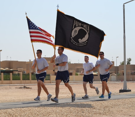 Airmen run with the U.S. flag and the National League of Families prisoner of war and missing in action flag during a 24-hour POW/MIA vigil walk at the 64th Air Expeditionary Group in Southwest Asia, Sept. 20, 2013. Participants volunteered for one-hour blocks, rotating the flags amongst themselves for a time. Many groups stayed longer or returned for a second round. (U.S. Air Force photo / Master Sgt. Dale Sickels)