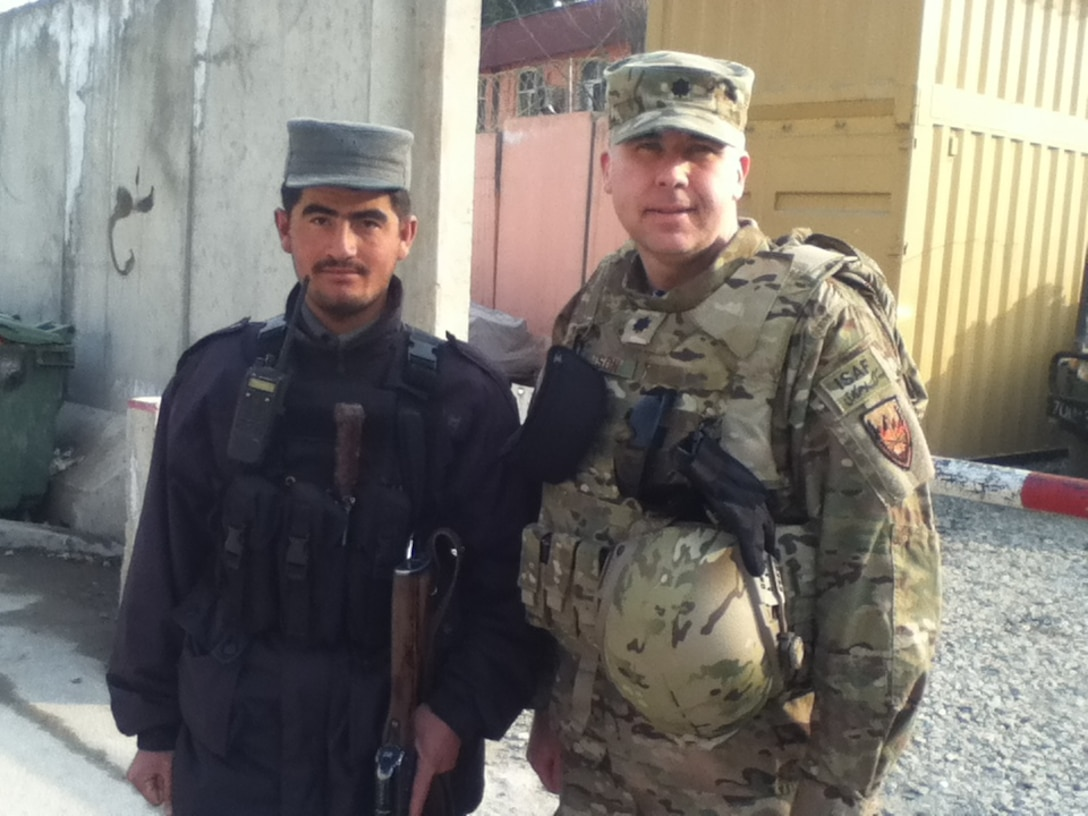 New York Air National Guard Lt. Col. Charles H. Hutson, Commander of the 174th Attack Wing Comptroller Flight, stands with a new member of the Afghan Local Police in the Kabul Green Zone during a recent six month deployment to Afghanistan. On September 7, 2013, Hutson received a Bronze Star for his deployed service as the Chief of Fiscal Policy, Force Reintegration Cell, Headquarters, International Security Assistance Force (ISAF) in support of Operation Enduring Freedom.  (Photo by Maj. Jeff Brown/Released).