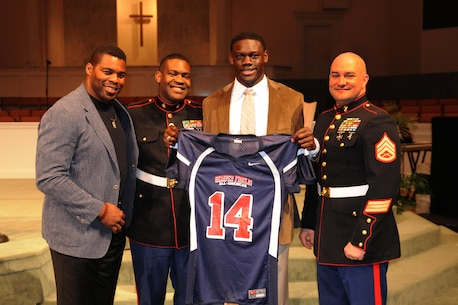 Marines of Recruiting Substation Savannah, Recruiting Station Jacksonville, Fla., present a Semper Fidelis All-American Bowl jersey to high school senior Milan Richard during a congratulatory ceremony at Calvary Baptist