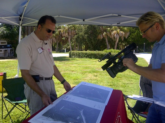 Frank Araico (left), project manager for the Mullet Key Bombing and Gunnery Range Formerly Used Defense Site, shows a local news reporter maps that detail where military activities took place on the site during World War II. A Remedial Investigation/Feasibility Study is currently under way.