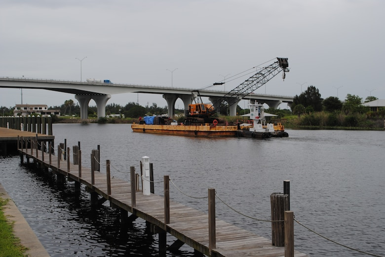 A barge pushes a crane underneath a bridge on the Caloosahatchee River at Moore Haven. The river is part of the 152-mile-long Okeechobee Waterway that allows boaters to travel by water from the Atlantic Ocean to the Gulf of Mexico.