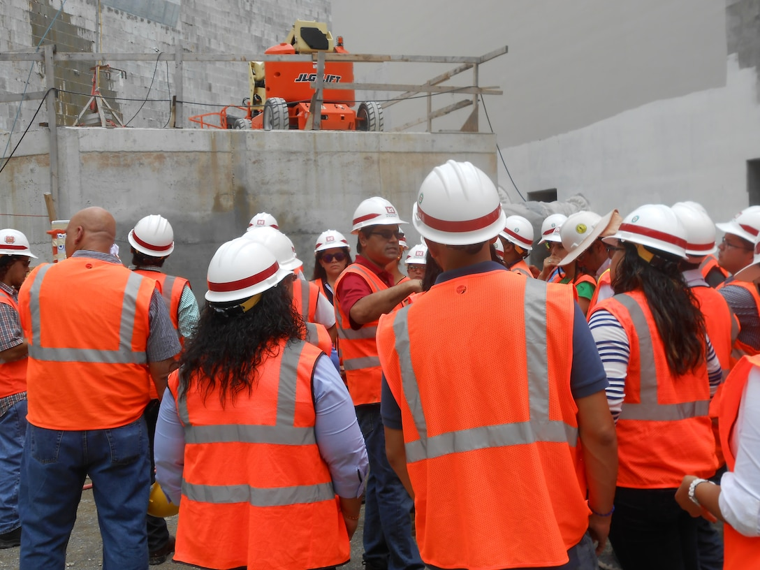 Pablo Vázquez-Ruiz (center) leads a tour of the Portugués Dam project for a group of engineering students from the American Concrete Institute, Polytechnic University of Puerto Rico.  As president of the Association of Engineers and Surveyors of Puerto Rico, Vázquez-Ruiz places a high priority on continuing education and on encouraging students to pursue degrees and careers in science, technology, engineering and math.