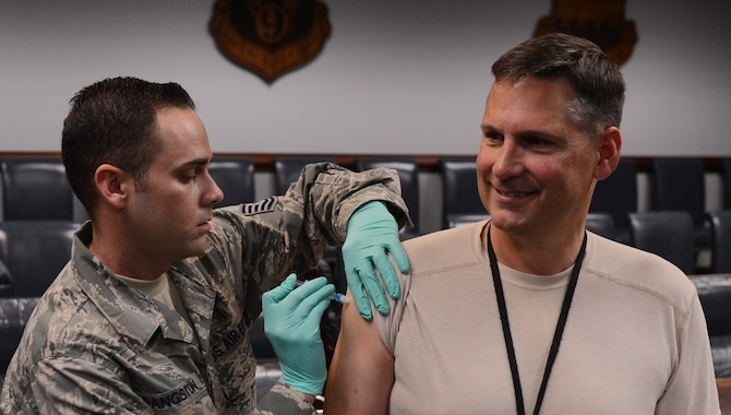 U.S. Air Force Tech. Sgt. Richard Sangston, 20th Medical Group allergy and immunizations technician, gives Col. Clay Hall, 20th Fighter Wing commander, his annual flu vaccination, Shaw Air Force Base, S.C., Oct. 11, 2013. All active-duty and medical personnel are required to receive their annual flu vaccination. (U.S. Air Force photo by Senior Airman Tabatha Zarrella/Released)