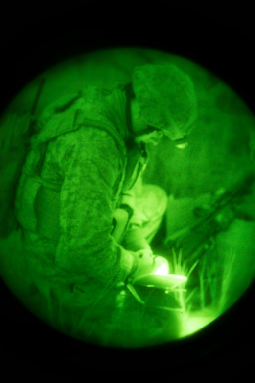 U.S. Marine Capt. Chris Walker, 1st Air Naval Gunfire Liaison Company Supporting Arms Liaison Team Delta joint terminal attack controller, annotates coordinates during a night close-air support scenario at Juniper Butte bombing range near Mountain Home Air Force Base, Idaho, Oct. 8, 2013. Air support in the exercise came from 391st Fighter Squadron F-15E Strike Eagles, Republic of Singapore Air Force F-15SG Strike Eagles, U.S. Navy AV-8B Harriers and German Air Force AG-51 Tornados. (U.S. Air Force photo by Master Sgt. Kevin Wallace/RELEASED)