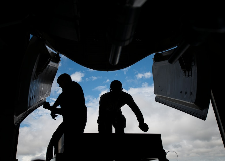 Two 437th Maintenance Squadron crew chiefs work on the front gear of a C-17 Globemaster III while the aircraft is lifted off the ground using jacks Oct. 7, 2013, at Joint Base Charleston, S.C. A team of eight crew chiefs used six jacks to raise a C-17 Globemaster III off the ground to change a tire and inspect the gears. (U.S. Air Force photo/ Senior Airman Dennis Sloan)