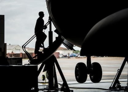 Senior Airman Robert Haberman, 437th Maintenance Squadron crew chief, walks up the stairs of a C-17 Globemaster III while the aircraft is lifted off the ground with jacks Oct. 7, 2013, at Joint Base Charleston, S.C. To raise a C-17 off the ground eight jacks and six crew chiefs are required. (U.S. Air Force photo/ Senior Airman Dennis Sloan)