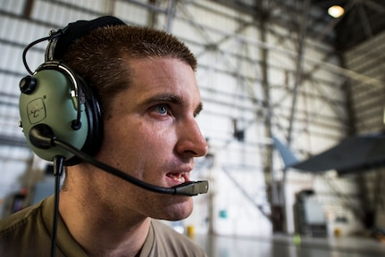 Staff Sgt. Ryan Sova, 437th Maintenance Squadron crew chief, uses a head set to communicate with another Airman in the cockpit while raising a C-17 Globemaster III using jacks Oct. 7, 2013, at Joint Base Charleston, S.C. A team of eight crew chiefs used six jacks to raise a C-17 Globemaster III off the ground to change a tire and inspect the gears. (U.S. Air Force photo/ Senior Airman Dennis Sloan)