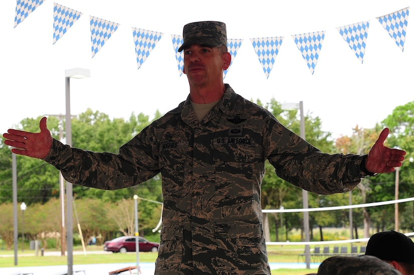 Chief Master Sgt. Shawn Hughes, 437th Airlift Wing command chief, gives opening remarks before the 2013 Oktoberfest Oct. 11, 2013, at Joint Base Charleston - Air Base, S.C. Oktoberfest is an annual event put together by the Top 3 for ranks E-1 through E-6 to show appreciation for their day-to-day hard work. The event included free food and drinks, a disc jockey and a hot wing eating contest. Airmen also played games such as basketball and cornhole. (U.S. Air Force photo/Airman 1st Class Chacarra Neal)